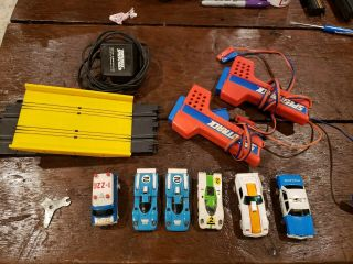 Vintage 6 Slot Cars Plus Matchbox Controllers,  Power Cord And Tilt Table.